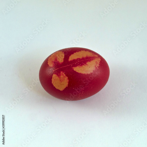 traditional red easter egg with natural leaves imprints