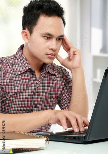 concentrating man working with laptop at his desk