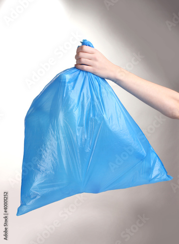 blue garbage bag with trash in hand isolated on white