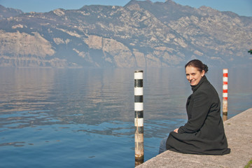 Young woman is sitting on the bank of lake Garda, Italy