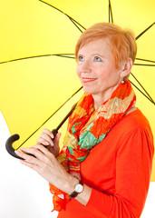 Gut gelaunte Seniorin mit Regenschirm