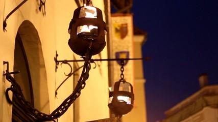 Evening fire burns in an old street lamp