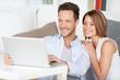 glückliches junges paar mit laptop vor dem sofa