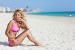 Bikini model sitting on the sand