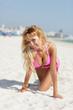 Sexy bikini model crawling on the sand