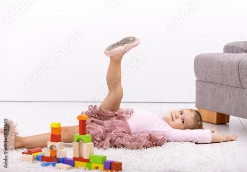 Little ballerina posing on floor