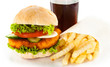 Big hamburger, French fries and vegetables on white background