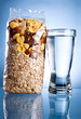 Glass of water and Opened Pack of muesli on a blue background