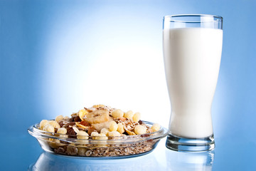 Dish of muesli and glass of fresh milk on a blue background