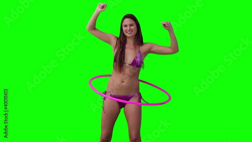 Woman spinning a hula hoop with her arms raised