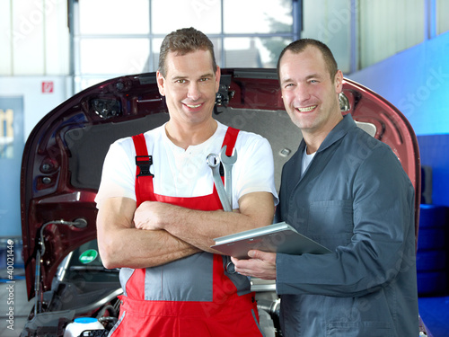 Two motor mechanics in a garage checking the engine bay