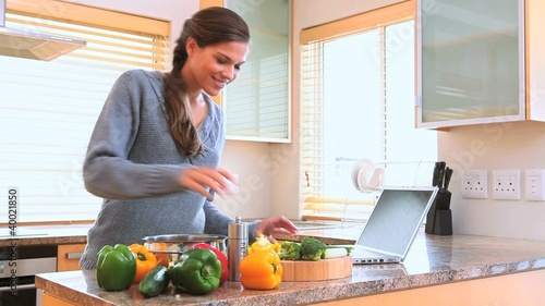 Woman cooking while looking at the recipe