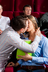 Couple in cinema with popcorn kissing