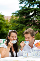 Couple drinking coffee in their garden