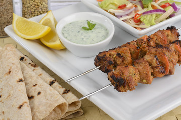 Chicken Tikka Kebab on skewers with raita, salad & chapatis