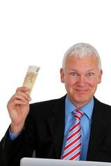 Geschaeftsmann Geldscheine vor Laptop