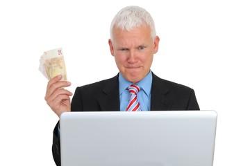 Geschaeftsmann mit Geld vor Laptop auf Couch