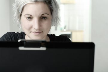 Frau sitzt am Computer und schaut auf Bildschirm