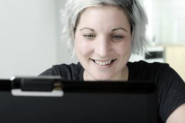 Lachende Frau mit Notebook