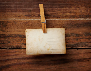 old photo postcard and clothes peg on wood