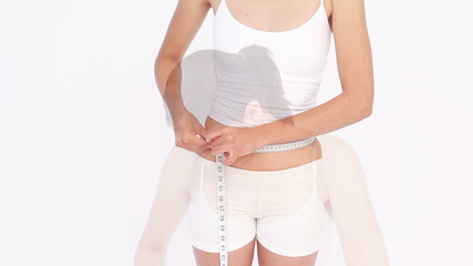 Portrait of a woman measuring her waist