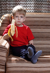 little boy in a red shirt eating a banana in a chair