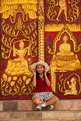 Pretty Thai woman sitting front of Thai art door in temple .