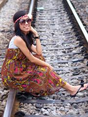 Young pretty Asian girl sitting on railway