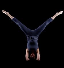 Woman in dark dress stand on hands - yoga asana