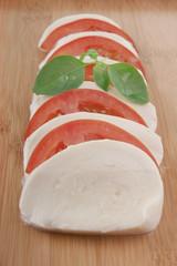 fresh mozzarella on chopping board with tomato and basil