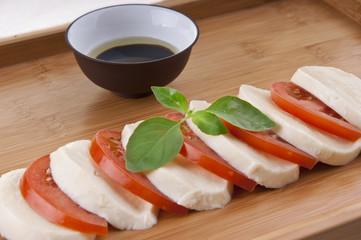fresh mozzarella on chopping board with tomato basil