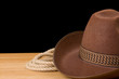 brown cowboy hat and rope isolated on black