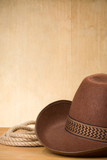 brown cowboy hat and rope on wood