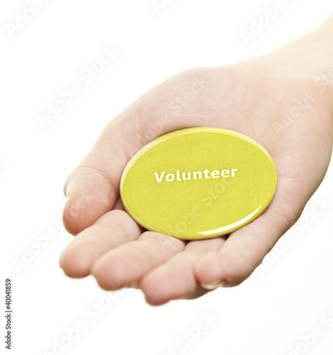 Hand holding volunteer button