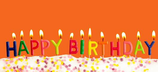 Happy birthday lit candles on orange background