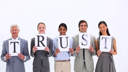 Business team holding letters that make the word TRUST