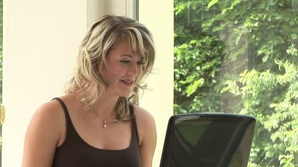 Junge Frau arbeitet am Computer am Fenster