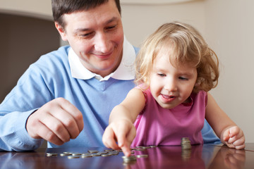 Dad and daughter puts coins