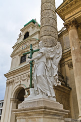 Angel statue with cross in front of Karlskirche (St. Charles's C