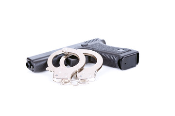 gun and steel handcuffs lying on the white background