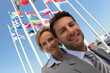 Businessman and woman with flags.