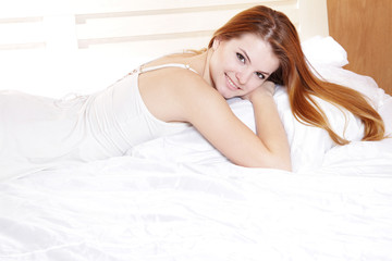 young smiling woman in bed