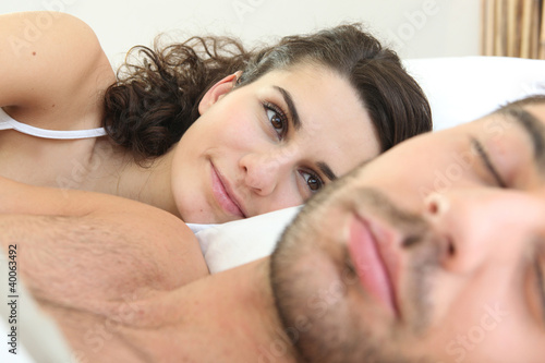 Woman looking at her husband sleeping