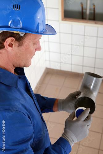Plumber holding plastic pipe