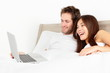Couple with laptop in bed