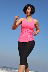 Pretty brunette is jogging at the beach, with her music