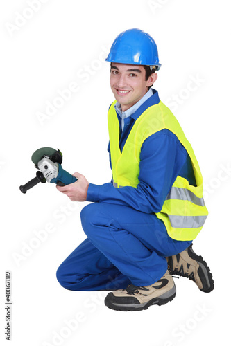 A male construction worker with a grinder.