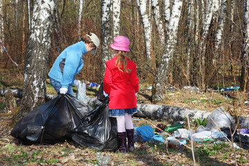 Brother and sister with black bags collect last year trash