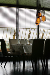 table with white tablecloth and serving and chairs in restaurant