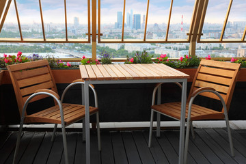 Wooden chairs and table at terrace in empty restaurant
